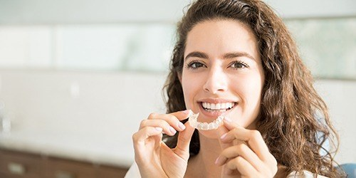brunette woman putting in invisalign