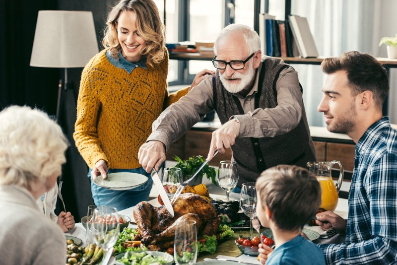 a family seated around the table preparing to eat Thanksgiving dinner